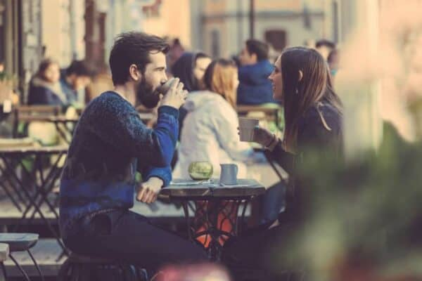 A man and woman sitting in a cafe talking