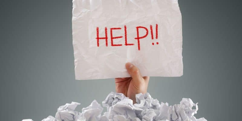 """Hand emerging from a pile of screwed up paper, holding a sign saying """"Help!"""""""